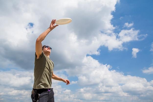 Uomo allegro che cattura il disco di plastica Foto Gratuite