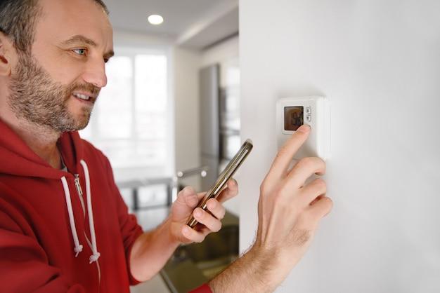 Uomo allegro che esamina il suo smartphone come viene regolata la temperatura della stufa in una casa intelligente Foto Premium