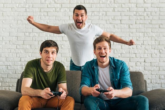 Uomo allegro che incoraggia per gli amici che giocano video gioco a casa Foto Gratuite