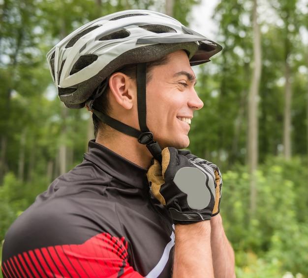 Uomo allegro che indossa il suo casco sportivo e distogliere lo sguardo. Foto Premium