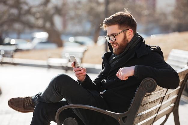 Uomo allegro che si siede e che utilizza smartphone nella città Foto Gratuite