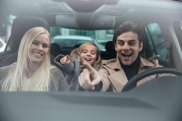 Uomo allegro che si siede in automobile con sua moglie e figlia Foto Gratuite