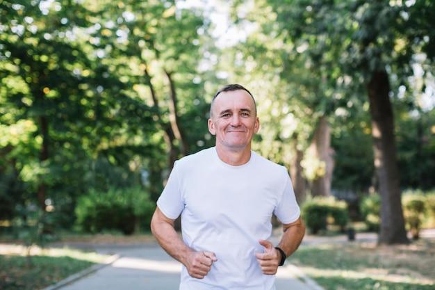 Uomo allegro in maglietta bianca che funziona in un parco Foto Gratuite