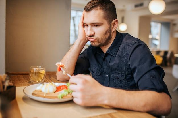Uomo annoiato e triste è seduto al tavolo e al caffè. ha in mano un pezzo di verdura sulla forchetta. l'uomo lo sta guardando ed espirando. Foto Premium