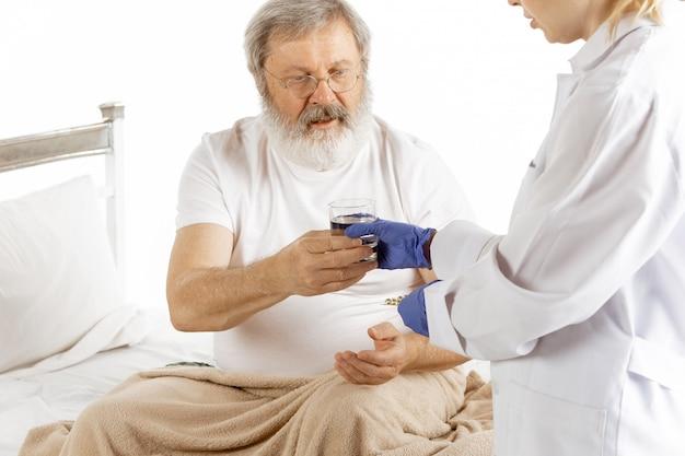 Uomo anziano anziano che recupera in un letto di ospedale isolato su bianco Foto Gratuite