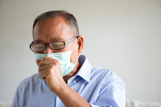 Uomo anziano asiatico che indossa maschera protettiva e tosse Foto Premium