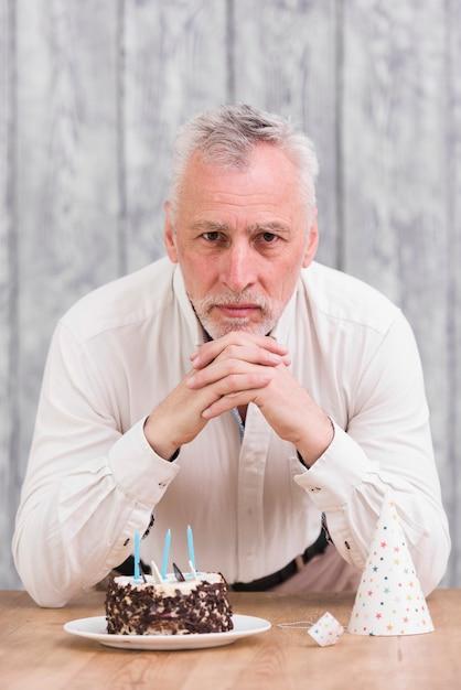 Uomo anziano bello che guarda l'obbiettivo con torta deliziosa e cappello del partito sul tavolo Foto Gratuite