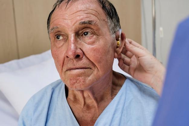 Uomo anziano che indossa apparecchi acustici Foto Premium