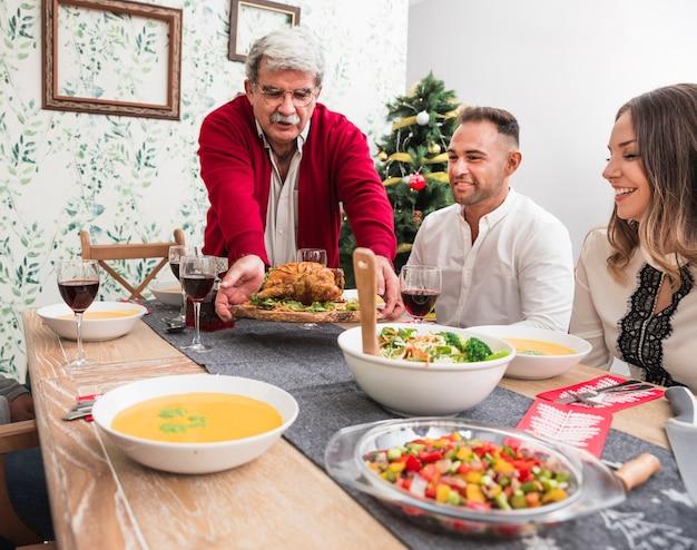 Uomo anziano che mette pollo al forno sulla tavola di natale Foto Gratuite