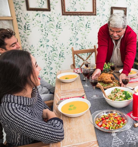 Uomo anziano che mette pollo arrostito sulla tavola festiva Foto Gratuite