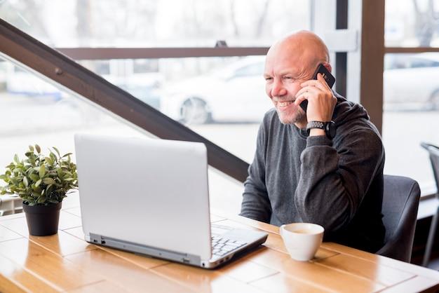 Uomo anziano che parla dal telefono cellulare Foto Gratuite