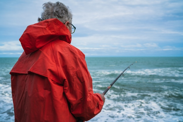 Uomo anziano che pesca nel mare. Foto Gratuite
