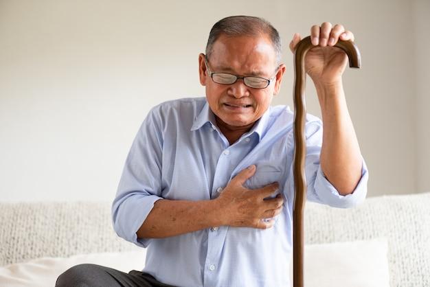 Uomo anziano che si siede sul sofà e che ha a con dolore sul cuore. concetto di assistenza sanitaria senior. Foto Premium