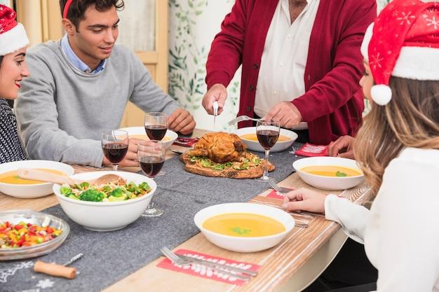 Uomo anziano che taglia pollo al forno sulla tavola di natale Foto Gratuite