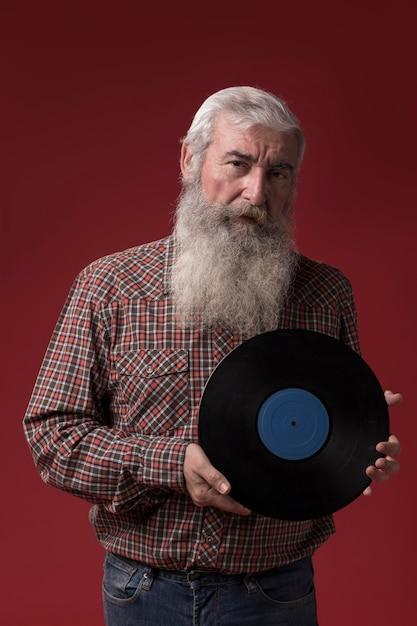 Uomo anziano che tiene un disco di vinile Foto Gratuite