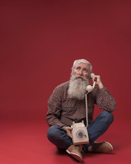 Uomo anziano che tiene un telefono Foto Gratuite