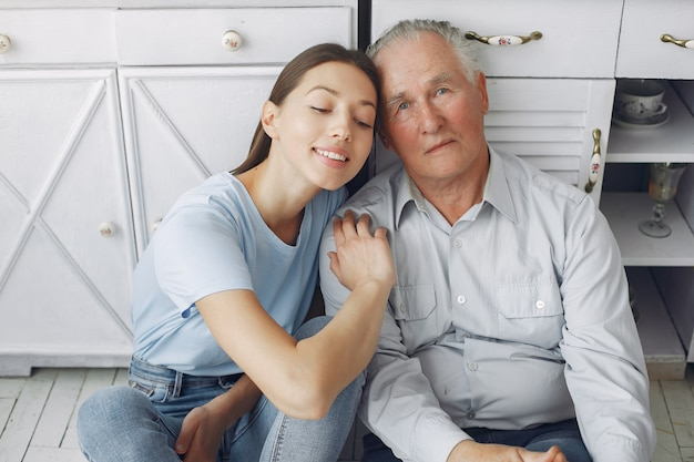 Uomo anziano in una cucina con la giovane nipote Foto Gratuite