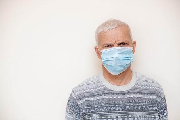 Uomo anziano nell'isolato medico protettivo della maschera nel bianco. coronavirus consigli per anziani. uomini anziani di sicurezza. Foto Premium