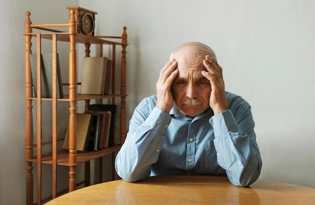 Uomo anziano preoccupato con la testa tra le mani Foto Premium