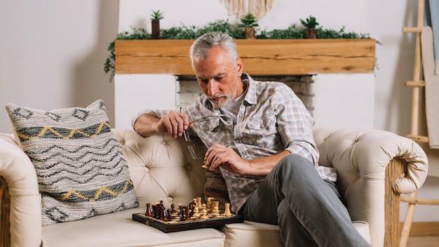 Uomo anziano seduto sul divano, giocare a scacchi a casa Foto Gratuite