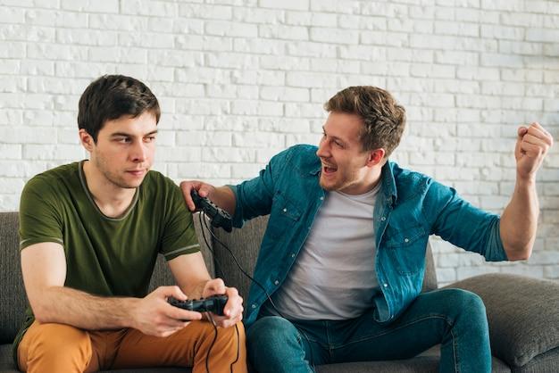 Uomo arrabbiato guardando uomo tifo dopo aver vinto il videogioco Foto Gratuite