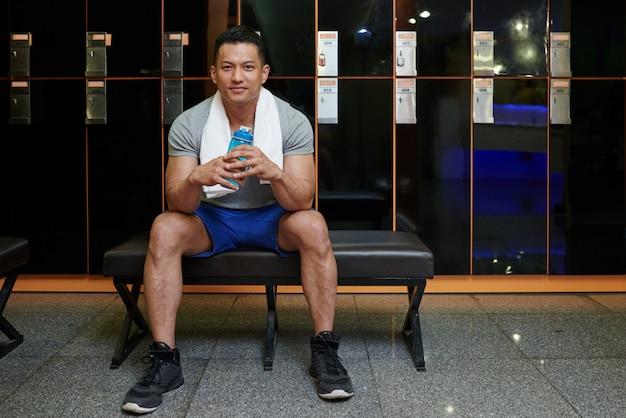 Uomo asiatico adatto che si siede sul banco nello spogliatoio in palestra e che tiene bottiglia di acqua Foto Gratuite
