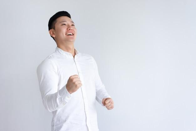 Uomo asiatico allegro che pompa i pugni e che osserva via Foto Gratuite