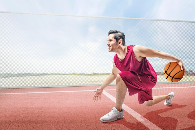 Uomo asiatico bello del giocatore di pallacanestro che gioca pallacanestro Foto Premium