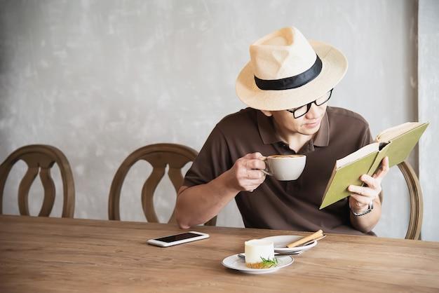 Uomo asiatico che beve un caffè e che legge un libro Foto Gratuite