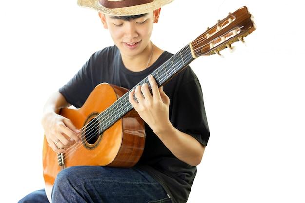 Uomo asiatico che gioca una chitarra classica isolata nella priorità bassa bianca. Foto Premium