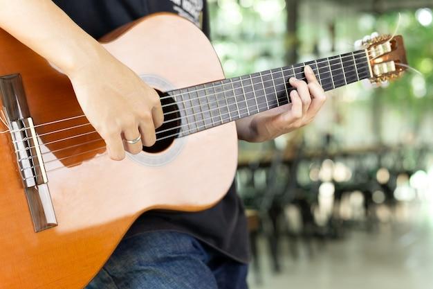 Uomo asiatico che gioca una chitarra classica nel fondo della sfuocatura. Foto Premium