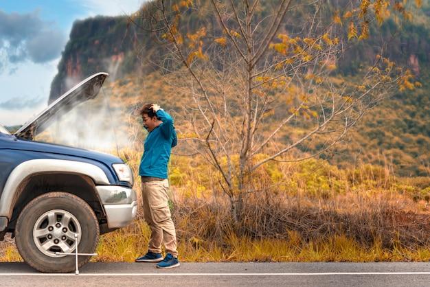 Uomo asiatico che ha problemi con la sua auto rotta Foto Premium