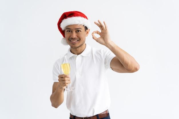 Uomo asiatico che mostra segno giusto e che tiene calice con champagne Foto Gratuite