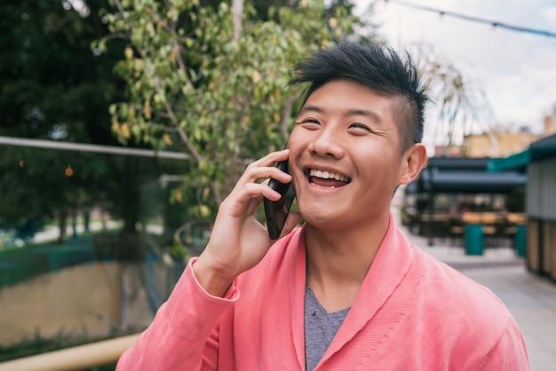 Uomo asiatico che parla al telefono all'aperto. Foto Premium