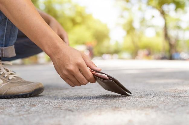 Uomo asiatico che seleziona portafoglio nero sulla strada nell'attrazione turistica Foto Premium
