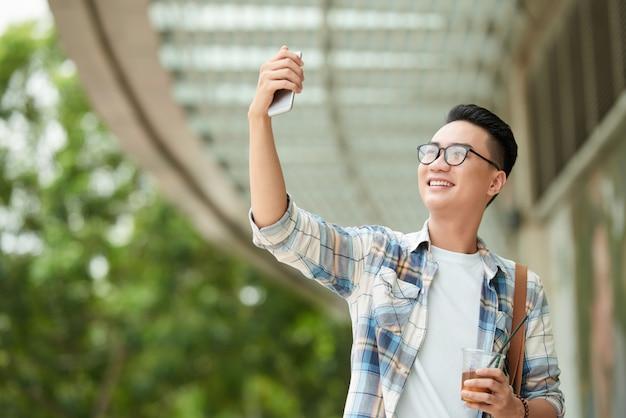 Uomo asiatico con indifferenza vestito che cammina attraverso il centro commerciale con la bevanda e che prende selfie sullo smartphone Foto Gratuite