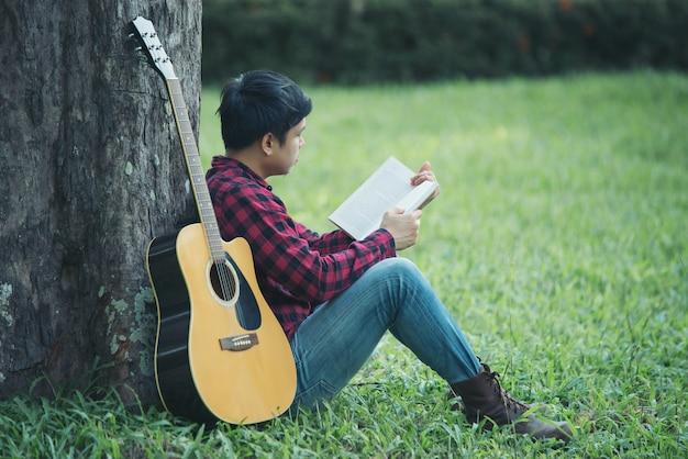 Uomo asiatico con la chitarra acustica in un parco Foto Gratuite