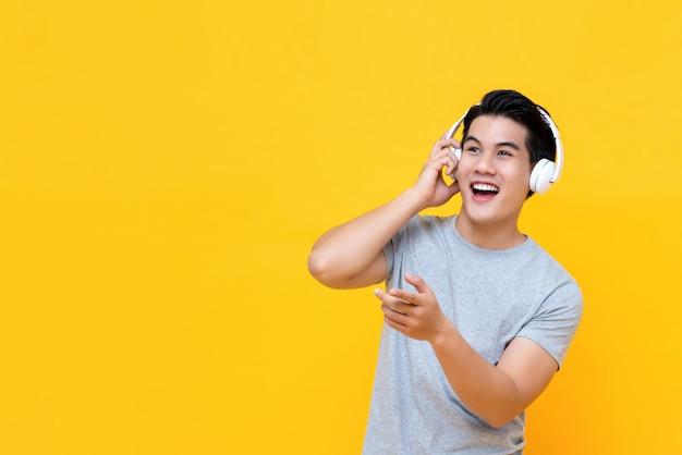 Uomo asiatico felice bello che ascolta la musica sulle cuffie e sul sorridere Foto Premium