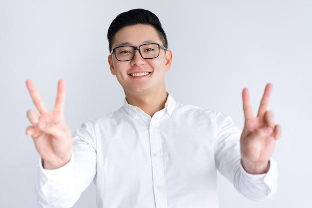 Uomo asiatico felice che mostra due segni di vittoria Foto Gratuite