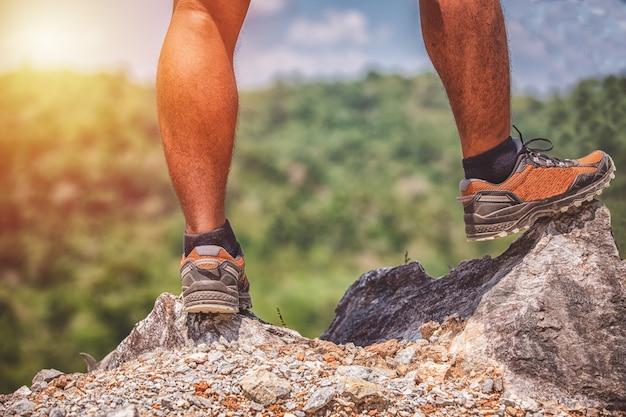 Uomo asiatico in piedi sul bordo di una scogliera in alto sopra le montagne Foto Premium