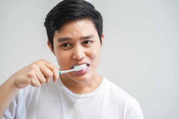 Uomo asiatico lavarsi i denti in bagno al mattino Foto Premium