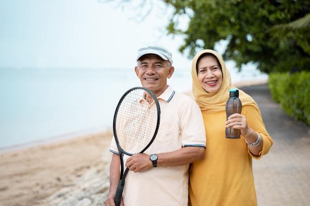 Uomo asiatico senior e donna che sorridono con la racchetta Foto Premium