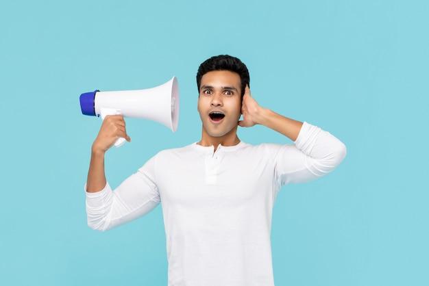 Uomo asiatico sorpreso che ascolta la voce sul megafono Foto Premium