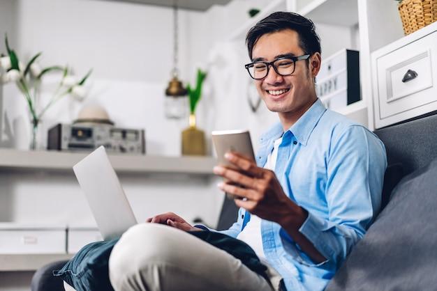 Uomo asiatico sorridente dei giovani che si rilassa facendo uso del funzionamento del computer portatile e della videoconferenza che si incontrano a casa. giovane uomo creativo che esamina il messaggio di battitura a macchina dello schermo con lo smartphone. lavorare da casa concetto Foto Premium