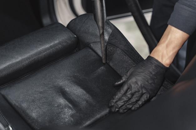 Uomo aspirapolvere una cabina auto in un garage Foto Gratuite