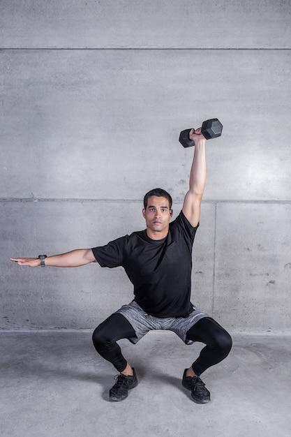 Uomo atletico che fa esercizio di dumbbell Foto Premium