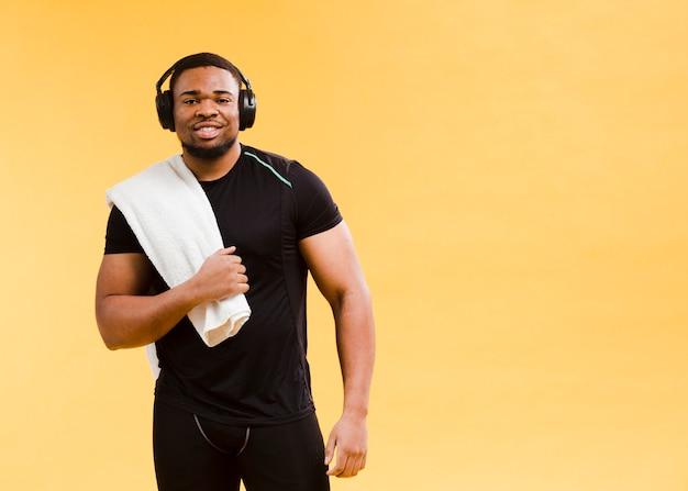 Uomo atletico che posa in attrezzatura e asciugamano della palestra Foto Gratuite