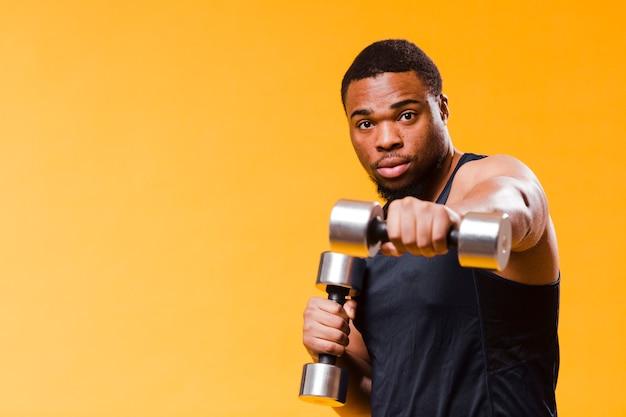 Uomo atletico che si esercita con i pesi e lo spazio della copia Foto Gratuite