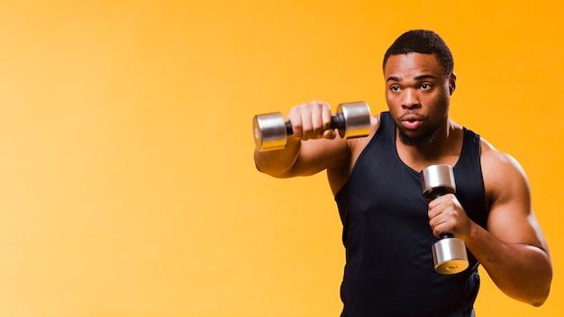 Uomo atletico che si esercita con i pesi Foto Gratuite