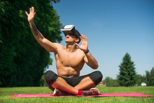 Uomo atletico che usando i vetri di una realtà virtuale all'aperto Foto Gratuite